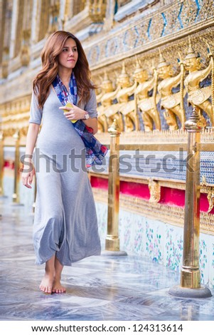 Tourist girl enjoying at Wat Phra Kaew, Temple of the Emerald Buddha, Bangkok, Thailand.
