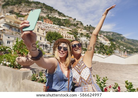 Tourist Girl Friends taking selfies  for social media with smart phone smiling on summer fun travel adventure in Amalfi