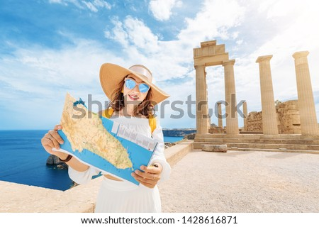 Tourist girl looking at map at the background of ancient Greek archaeological site and Acropolis. Travel the world and greatest landmarks.
