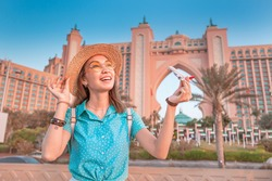 Tourist girl playing with toy white passenger airplane at the background of Hotel in Dubai sea resort. Concept of air travel and ticket prices