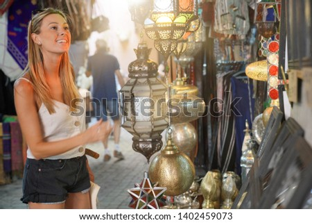 Tourist girl shopping in Moroccan souk of Marrakech