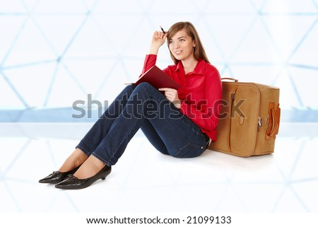 Tourist girl sitting on a suitcase with a notebook in her hand