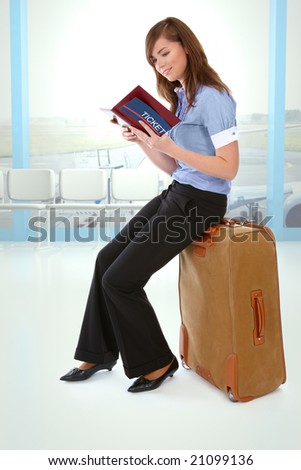 Tourist girl sitting on a suitcase with a ticket and notebook in her hand