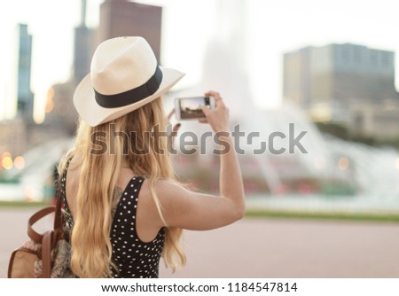 Tourist girl taking picture of buckingham fountain chicago and the skyline on the background