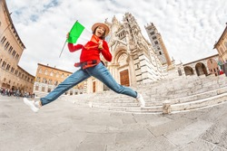 Tourist girl travels in Italy. Happy young hipster woman jumping with flag in front of the Duomo Cathedral in Siena. Vacation and sightseeing tour in Europe