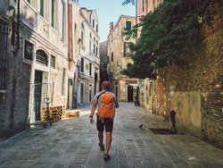 Tourist goes a view with his back to Venice, Italy with an orange backpack and camera on his neck along the old streets of the city