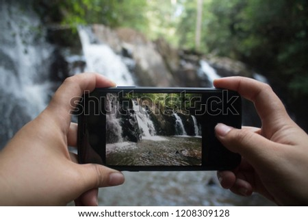 Tourist hand holding mobile phone taking a photograph of landscape waterfall in forest.