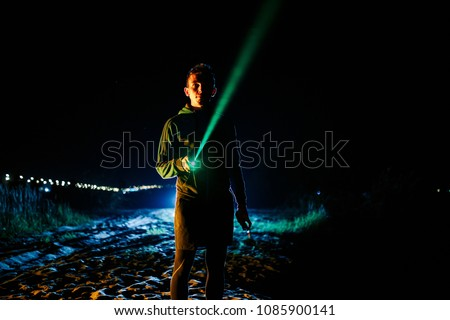 Tourist have rest in camp, lighting at the sky with green laser pointer. Grainy effect cinematic style. #1085900141