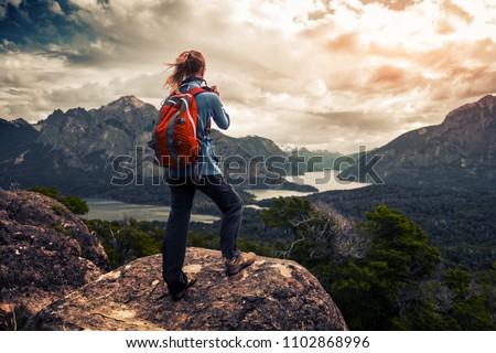 Tourist hiker with red backpack takes pictures of the valley with mountains and lakes. Patagonia, Argentina