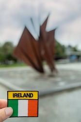 Tourist holding badge with National flag and sign Ireland in focus, Galway Hooker monument in Eyre Square out of focus.