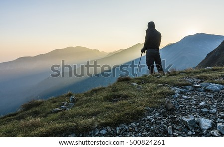 Tourist in a jacket with a hood and sticks trekking in the mountains. - Shutterstock ID 500824261