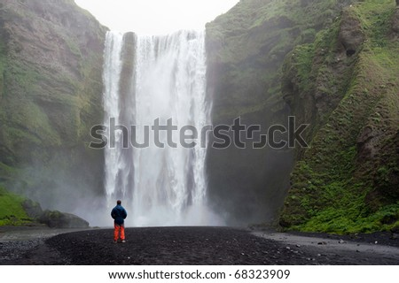 tourist in front of Skogafoss waterfall in Iceland