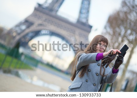 Tourist in Paris taking a picture of herself with Eiffel tower