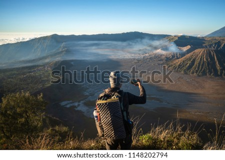 Tourist is standing on the viewpoint of the hill for take a look the beautiful scenery of fog, volcano and take picture by cell phone in the morning at Bromo Tengger Semeru National Park, Indonesia.