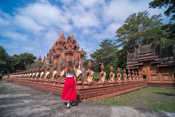 Tourist is talking a photo to post in social media at Wat Khao Angkhan or Wat Khao Pra Angkarn, the sandstone spires and Buddha statues in the temple located in Burirum province, Thailand