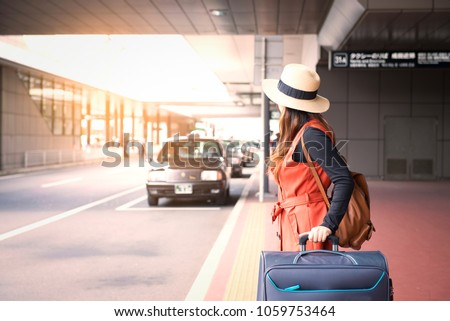 Tourist is waiting a taxi in front of Tokyo airport in Japan.