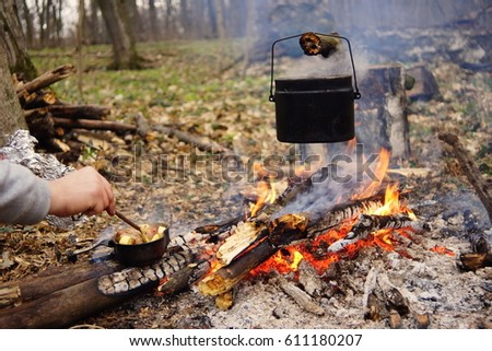 Tourist kettle on c& fire with tent on background. hand with stick about fire. & Royalty-free Tourist kettle on camp fire with tentu2026 #611327381 ...