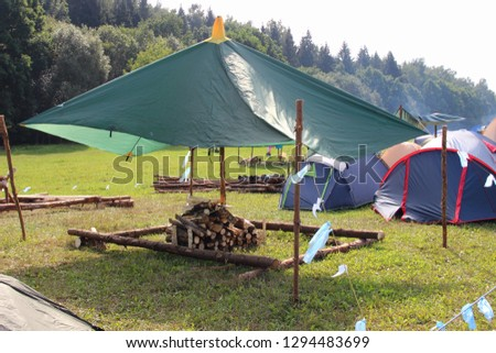 Tourist life - camp tent with a stack of firewood on the green grass field on the forest and tents background on summer day - sports tourism, camping, scouting #1294483699