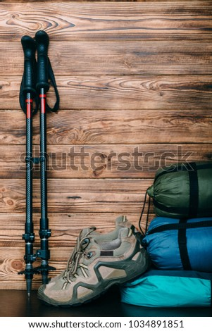 tourist lifestyle with trekking shoes, sleeping bags, tent and trekking poles on wooden background with copy space for text #1034891851