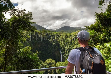 Tourist looking at the La Fortuna Waterfall in Costa Rica. The waterfall is located on the Arenal River at the base of the dormant Chato volcano. Foto stock ©