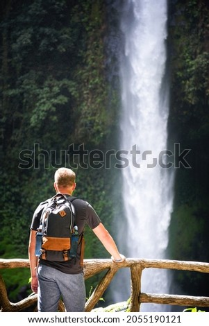 Tourist looking at the La Fortuna Waterfall in Costa Rica. The waterfall is located on the Arenal River at the base of the dormant Chato volcano. Zdjęcia stock ©