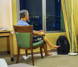 Tourist looks out the window of the hotel rooms at night Bangkok