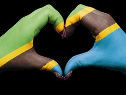 Tourist made gesture  by tanzania flag colored hands showing symbol of heart and love
