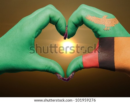 Tourist made gesture  by zambia flag colored hands showing symbol of heart and love during sunrise - stock photo