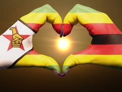 Tourist made gesture  by zimbabwe flag colored hands showing symbol of heart and love during sunrise