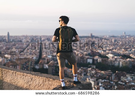 Tourist making photo of the city, Man with backpack enjoy beautiful city view, hipster using mobile phone, traveler mock up top of the city