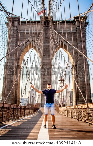 Tourist male model posing in front of Brooklyn Bridge pillar during sunny summer day in New York City, USA