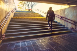 Tourist man in a hood with a large backpack climbs the stairs at dawn in an urban environment. Tourist in winter city concept