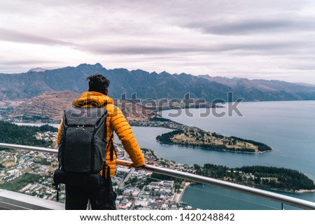 Tourist man looking down at Queenstown from Skyline Gondola attraction. View of city from viewpoint. Red, yellow. Romantic holiday, travel concepts. New Zealand. #1420248842