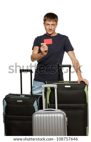 Tourist man of middle age standing with his travel suitcases, showing empty credit card, against white background