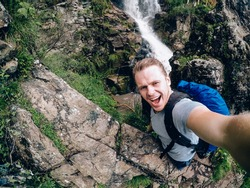 tourist man on a waterfall background holds an action camera and takes a picture of Selfie.