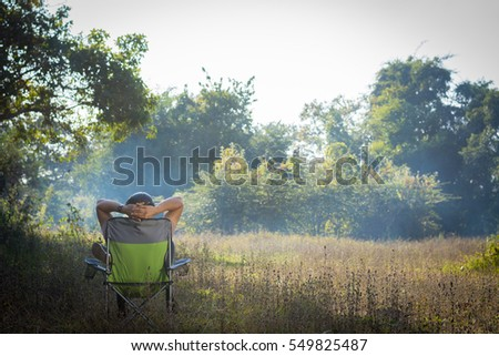Tourist man relax sitting on a field chair in the forest. Stock fotó ©