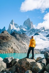 Tourist man & scenic view of snowcapped mountain tops of Mount Fitzroy, Patagonia trek. Blue sky, turquoise blue lake and scenic rock landscape. Shot in Argentina. Nature, travel, adventure, hiking.