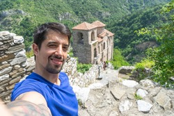 Tourist man smile take selfie on ancient fortress in eastern europe. Beard guy visit holy orthodox church in popular destination and fortification in Bulgaria. Tour in antique heritage monastery Assen