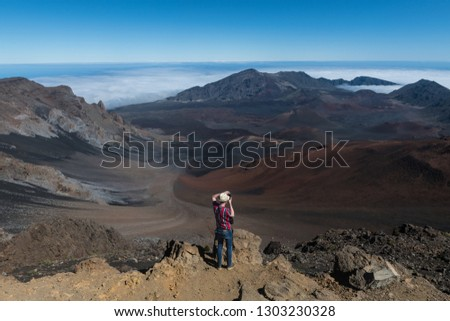 Tourist man taking photos of volcano mountain valley from the top on Big Island, Hawaii #1303230328