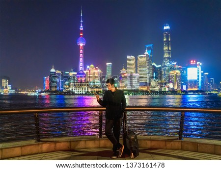 Tourist man using a smartphone near The Bund in Shanghai downtown, China in travel trip, vacation, or holidays concept in Asia. Skyscraper and high-rise buildings at night. #1373161478