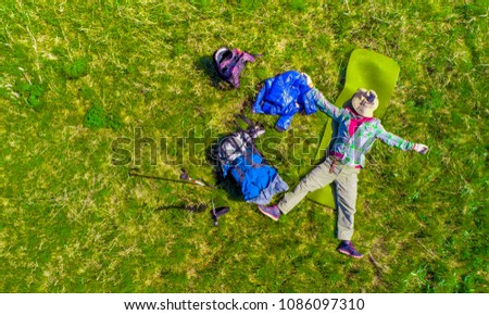 Tourist mountaineer tired lying on the ground on a halt after hiking in the mountains relaxes happy resting