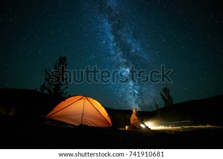 Tourist near his camp tent at night under a sky full of stars. Orange illuminated tent.