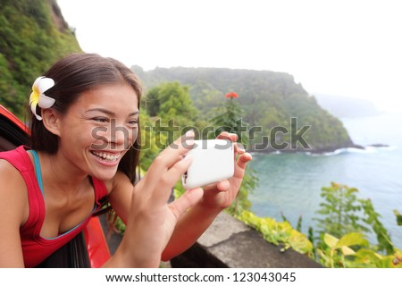 Tourist on Hawaii taking photo with camera phone during car road trip on the famous Road to