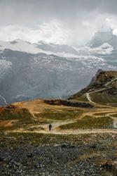 Tourist on path among snow mountains. Zermatt, Swiss Alps. Adventure and hiking in Switzerland, Europe.