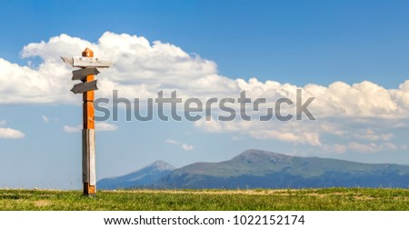 Tourist paths directions shown on wooden traditional direction sign in Carpathian mountains, Ukraine. High mountain peaks blurred on background. Sunny warm weather outdoors. Travel and hiking concept.