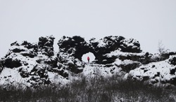 Tourist person red jacket standing in hole window of Dimmuborgir volcanic lava fields rock formation Myvatn Iceland