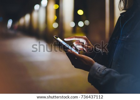 Tourist pointing finger on screen smartphone on background illumination glow bokeh light in night atmospheric city, hipster using in hands mobile phone, street in Barcelona, online internet concept