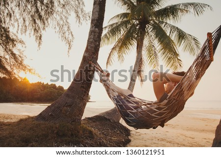 tourist relaxing in hammock on tropical beach with coconut palm trees, relaxation and leisure tourism