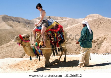 Tourist rides a camel of a Bedouin man in the Judaean Desert , Israel.