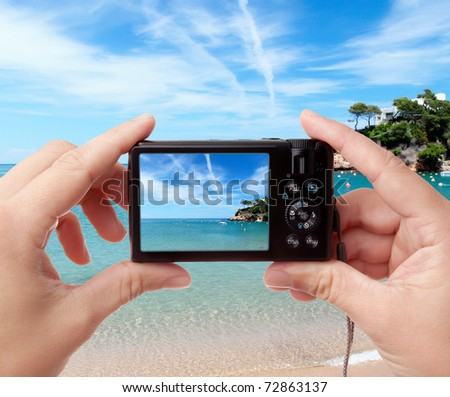 Tourist's hands holding digital photo camera on vacations, taking picture of beautiful sunny seaside
